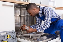 Man repairing broken dishwasher