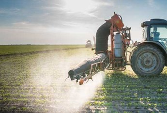 Tractor spraying pesticides in field